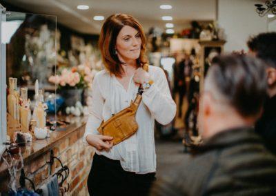 Frau zeigt Kunden senfgelbe Gürteltasche und Armband Uhr