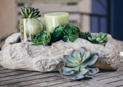 Kunstpflanzen und Kerzen in Schale aus Stein