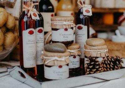 Gläser mit Honig und Flaschen mit Likören