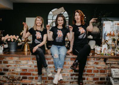 Drei Frauen auf Tresen immitieren Hühner