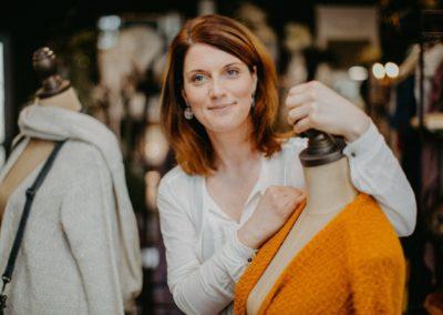 Frau neben senfgelber und weißer Strickjacke