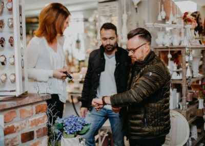 Frau berät zwei Männer beim Uhrenkauf