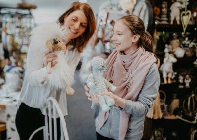 Frau zeigt Kind Plüschtiere