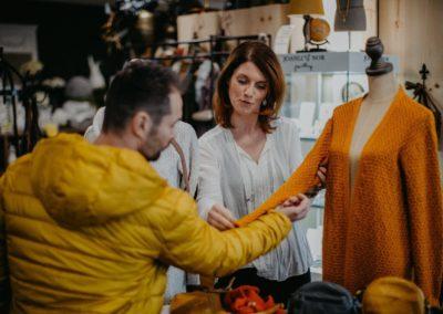Verkäuferin zeigt Kunden Strickjacke uns andere Produkte
