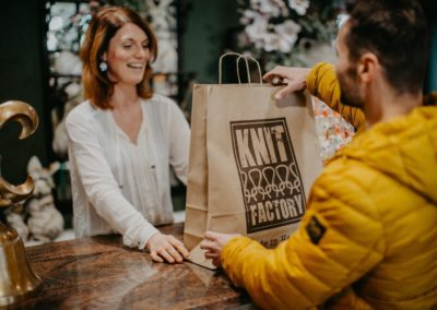 Verkäuferin gibt Kunden Einkaufstüte aus Papier mit Ware