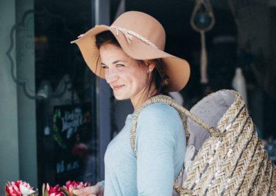 Frau trägt Sommerhut und Tasche aus Bast