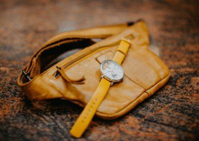 Uhr in senfgelb liegt auf senfgelber Gürteltasche aus Leder