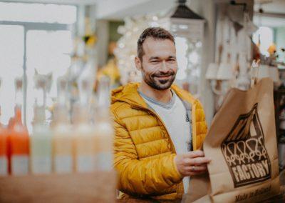 Zufriedener Mann nimmt Einkaufstasche entgegen