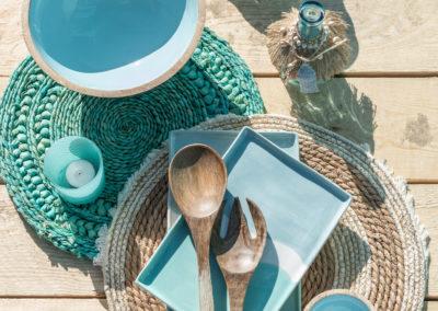 Holzbesteck mit blauen Akzenten und Schüssel aus Holz auf einem Tisch