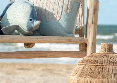 Türkisfarbene Kissen auf heller Holzbank mit Meer im Hintergrund