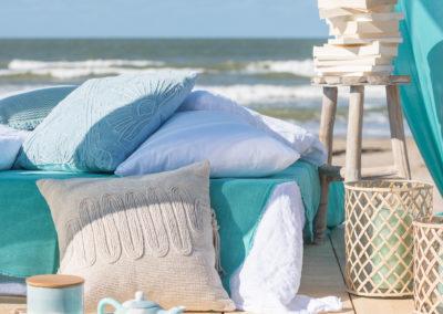 Kissen auf Holzmöbel mit Meer im Hintergrund