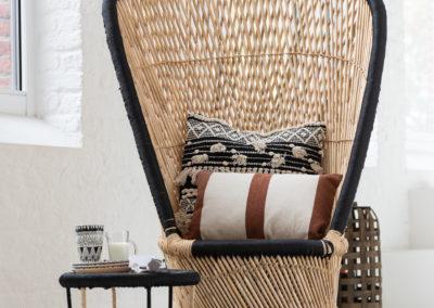 geflochtener Sessel mit bedruckten Kissen