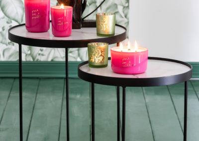 Fuchsiafarbene Kerzen und grüne Teelichthalter auf Tisch zur Dekoration