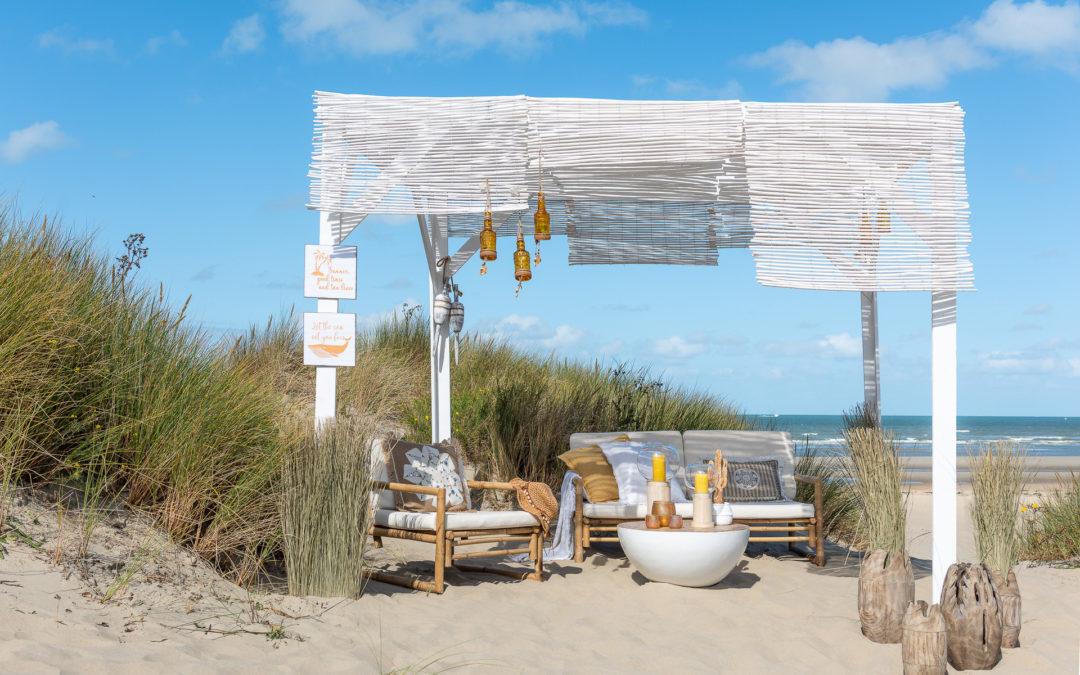 Weiße Deko Artikel Holzbank und Holzsessel am Strand mit Meer im Hintergrund