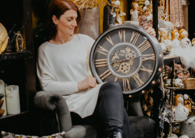 Frau mit Deko Uhr im Schoß sitzt auf einem Sessel im Deko Laden