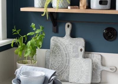 Küche mit Geschirr, Holzbrettchen, Vasen und Stövchen