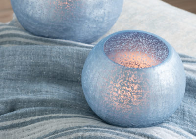 Zwei blaue Teelichthalter auf einer Stoffdecke