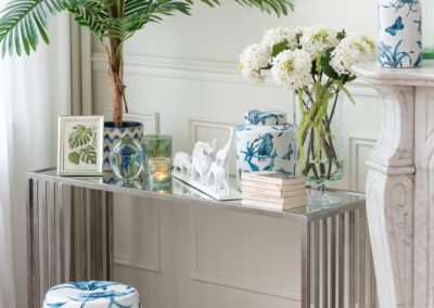 weißes Interieur mit blau-grünen Mustern auf Vasen und Hocker