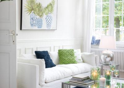 blaue und grüne Möbel stehen vor weißer Wand