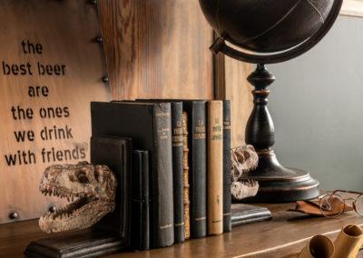 Brauner Globus aus Holz steht neben Büchern auf nostalgischem Schrank