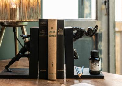 Dunkelbraune Bücherstütze mit geschnitzter Holzfigur