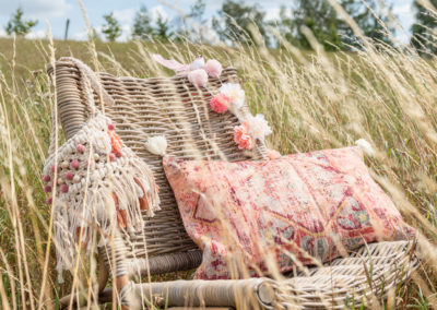 Sessel aus geflochtenem Holz mit indischen Kissen steht im Kornfeld