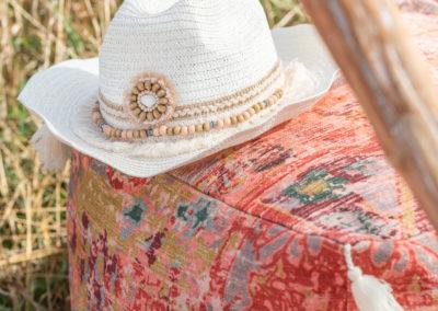 Geflochtener Hut liegt auf Textil Hocker mit indischem Muster