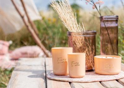 Pfirsichfarbene Keramik Becher und Glaswaren auf einem Holztisch