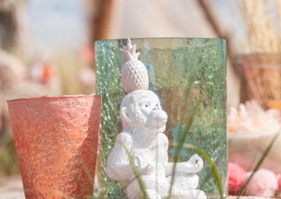 Affe als Porzellan Figur und farbige Glasvasen stehen auf Holztisch