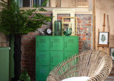Grüne Wandkommode mit braunem Holzsessel steht im gestylten Loft