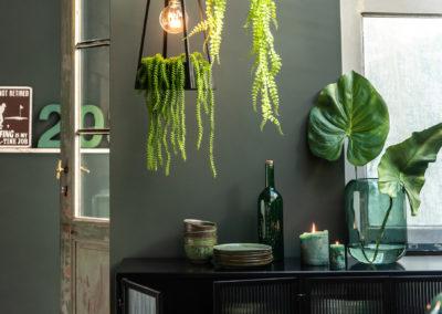 Dunkle Möbel und grüne Pflanzen mit brennenden Kerzen