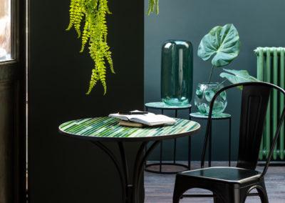 Grüner runder Tisch mit aufgeklapptem Buch und dunkler Stuhl, dazu hängen grüne Pflanzen von der Decke