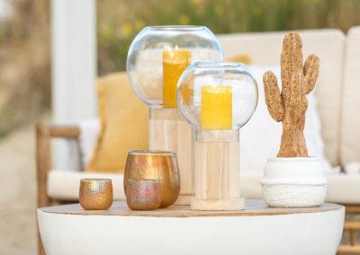 Ockerfarbene Gläser und Kerzen auf einem weißen Beistelltisch