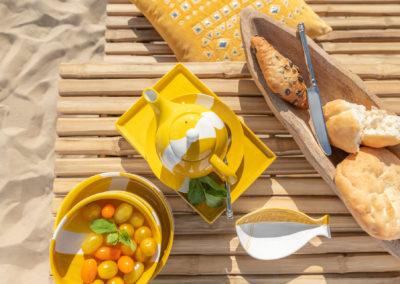 Mit gelb-weißem Geschirr gedeckter Holztisch