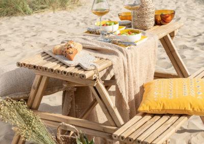 Gedeckter Holztisch steht am Strand