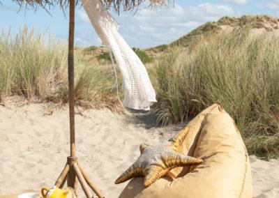Sitzsack steht neben einem Sonnenschirm am Strand