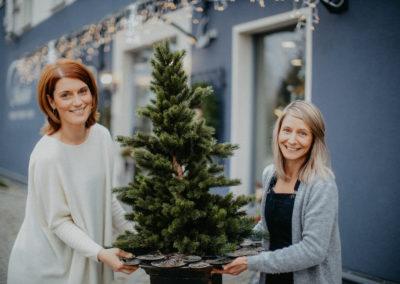 Zwei Frauen tragen einen künstlichen Weihnachtsbaum