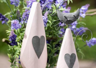 Zwei Holz Figuren mit Lavendel Strauch im Hintergrund