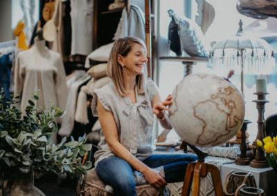 Frau mit Leinen Mode vor einem großen Globus