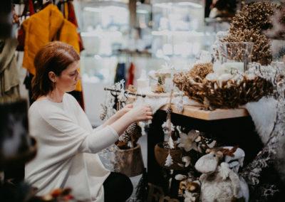 Konzentrierte Frau beim Einrichten der Weihnachtsdekoration im Laden