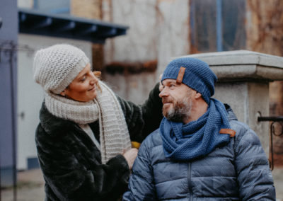 Mann und Frau mit Mütze und Schal gekleidet blicken sich freundlich an