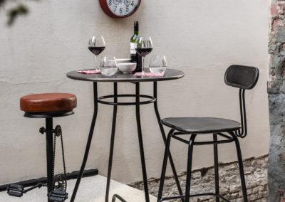 Bistrotisch mit einem Lederstuhl und Metallstuhl, dazu Weingläser und rote Uhr im Hintergrund