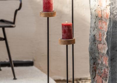 Drei Kerzenständer aus lackiertem Metall mit Holzfuß und Kerzenhalter aus Holz mit roter Kerze