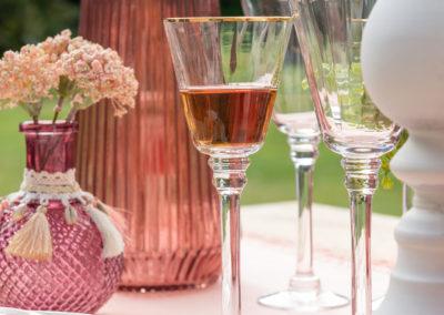 Weiße und pfirsichfarbene Glaswaren mit Federn geschmückt