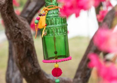 Glasflasche mit bunten Bommeln hängt an Baum mit bunten Blüten