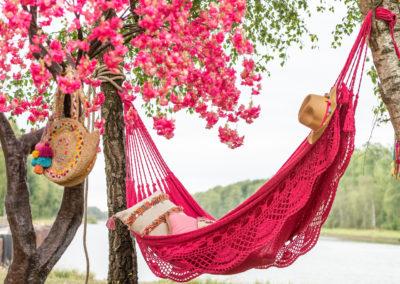 Bunte Hängematte und zwei Taschen die an Baum hängen