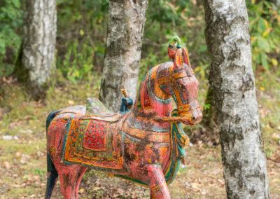 Buntes Spielzeugpferd aus Holz auf Rollen steht im Wald