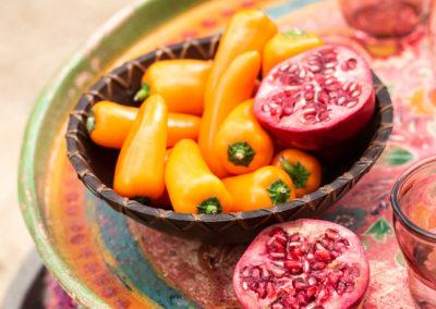 Bunte Vintage Schale mit aufgeschnittenem Granatapfel und Paprika