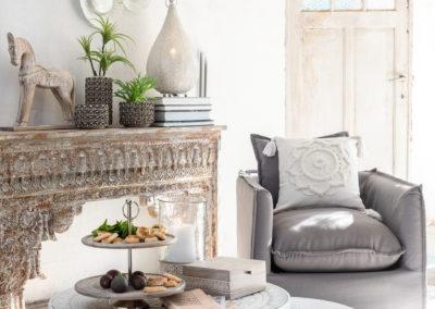 Weiße Kissen auf grauem Sessel mit Deko im Haus