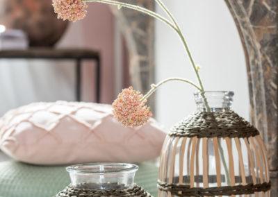 Zwei Vasen aus Glas mit Holzgeflecht ringsum, im Hintergrund Textil Kissen